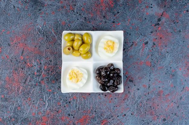 Gekookt ei met zwarte en groene gemarineerde olijven.
