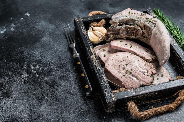 Gekookt gekookt kalfsvlees of rundertong gesneden in een houten bakje. bovenaanzicht.