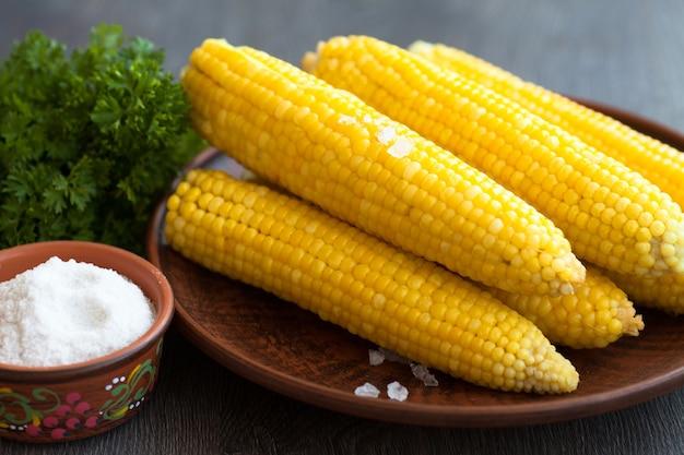 Gekookt maïs met solt op een plaat op houten achtergrond