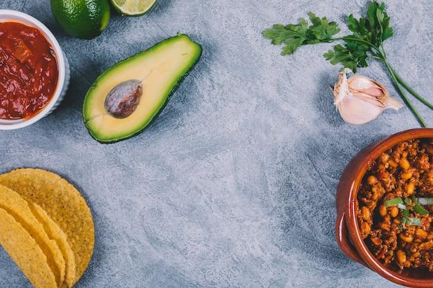 Gekookt rundergehakt; gehalveerde avocado; koriander en knoflook op concrete achtergrond