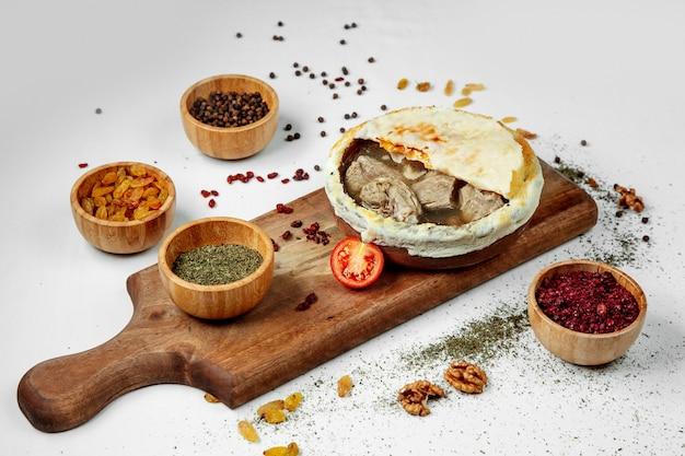 Gekookt vlees in een kleikom die met brood op een houten raad wordt behandeld