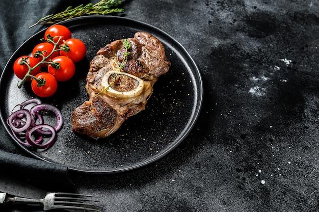 Gekookt vlees met been osso buco in tomatensaus. ossobuco vleesstoofpot. zwarte achtergrond.