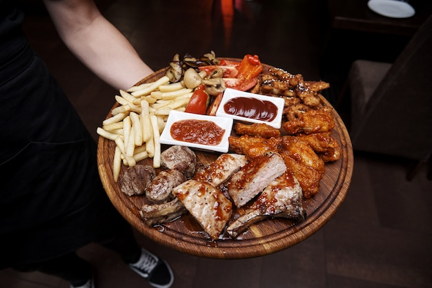 Gekookt vlees met groenten op een houten bord in de handen van de ober.
