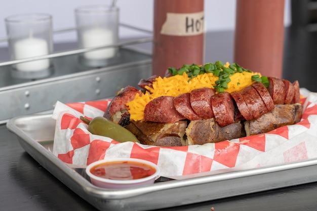 Gekookte aardappel gevuld met geroosterde worstjes cheddar kaas groene uien met jalapeno en saus