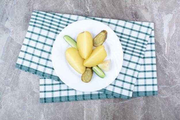 Gekookte aardappelen en diverse augurken op een witte plaat.