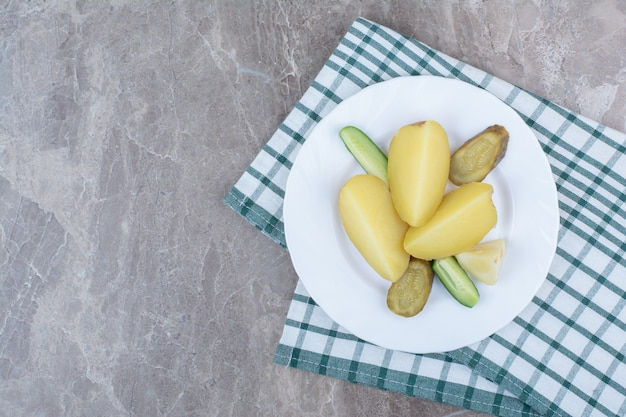 Gekookte aardappelen en diverse groenten op witte plaat.