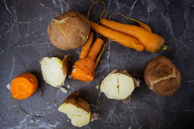 Gekookte aardappelen en wortelen liggen op een donkergrijze achtergrond.