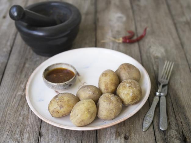Gekookte aardappelen in hun schil. geheel met rode peper, zout en pikante saus op witte plaat, oude houten tafel, rustieke stijl. sluit omhoog, kopieer ruimte.