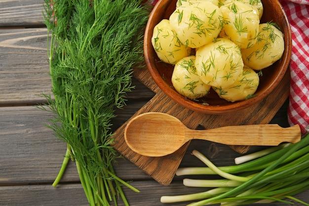 Gekookte aardappelen met groenen in kom op tafel
