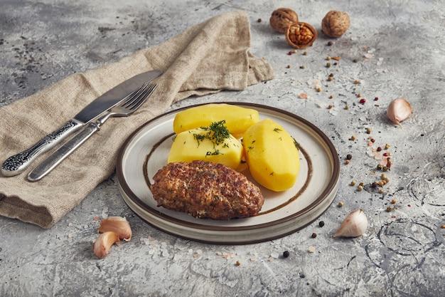 Gekookte aardappelen met kotelet, lichte achtergrond