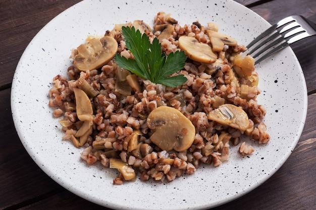 Gekookte boekweit met gestoofde champignons. russische traditionele gerechten. gezonde voeding eten. kopieer ruimte, bovenaanzicht.