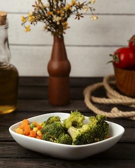 Gekookte broccoliwortelen en graan op een houten lijst