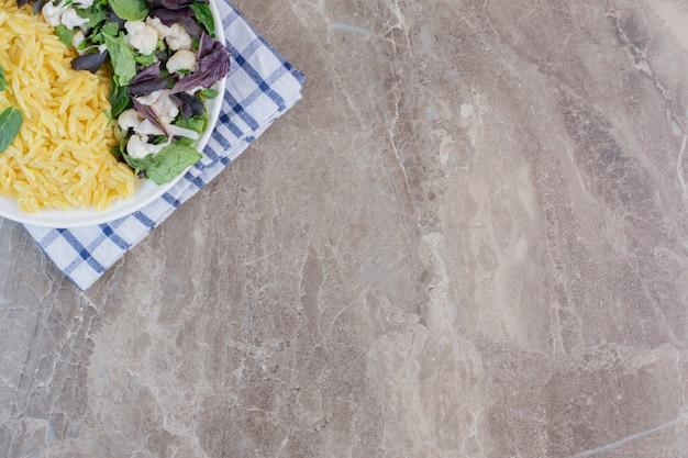 Gekookte bruine rijst met smakelijke salade op een plaat op marmer.