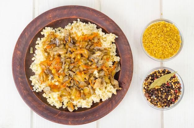Gekookte bulgur grutten met gestoofde groenten en champignons, vegetarisch eten