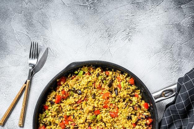 Gekookte bulgur met groenten in een pan. grijze achtergrond