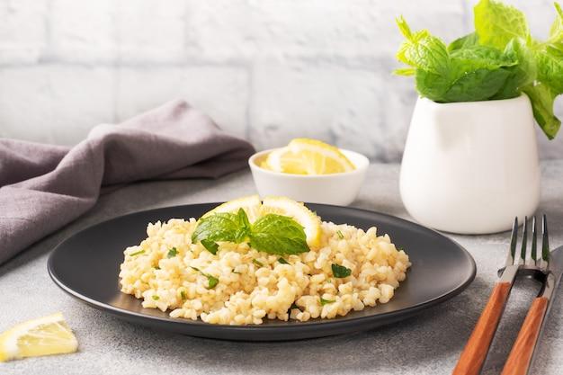 Gekookte bulgur met verse citroen en munt op een bord. een traditioneel oosters gerecht genaamd tabouleh. grijze betonnen achtergrond