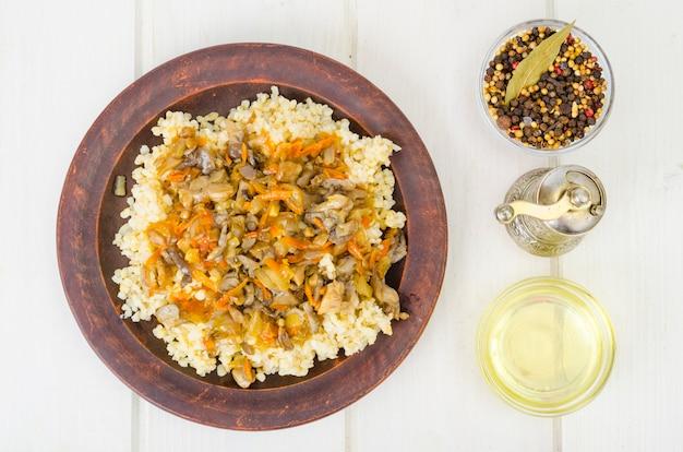 Gekookte bulgurgrutten met gestoofde groenten en champignons