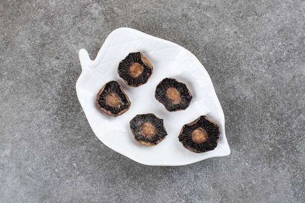 Gekookte champignonpaddestoelen op witte plaat.
