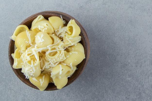 Gekookte conchiglie pasta in houten kom.