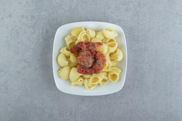 Gekookte conchiglie pasta met gemarineerd vlees op witte plaat.