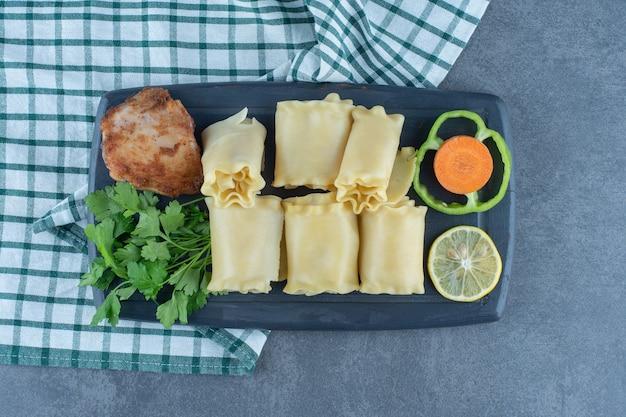 Gekookte deegbroodjes en geroosterde kip op donker bord.