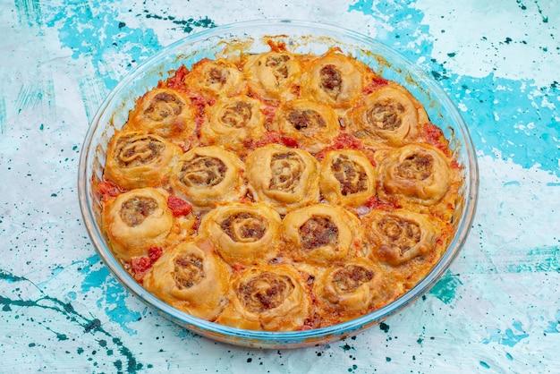 Gekookte deegmaaltijd met gehakt en tomatensaus in glazen pan op helderblauw bureau, het koken van het deeg van het bakvoedselvlees