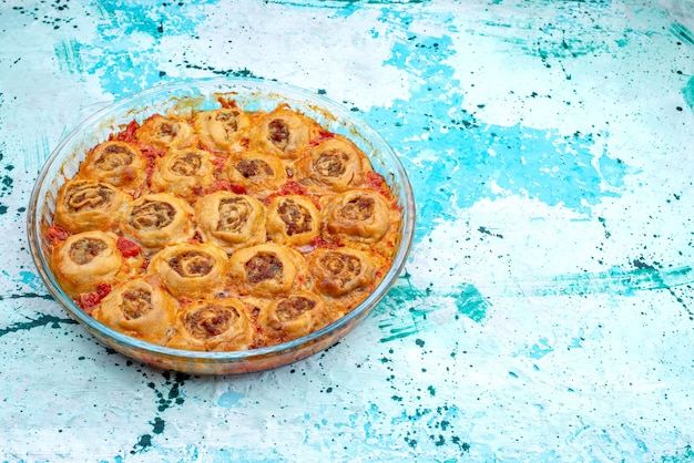 Gekookte deegmaaltijd met gehakt en tomatensaus in glazen pan op helderblauw, koken bakvoedsel vleesdeeg