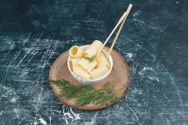 Gekookte deegwaren in witte kom met eetstokjes en koriander.