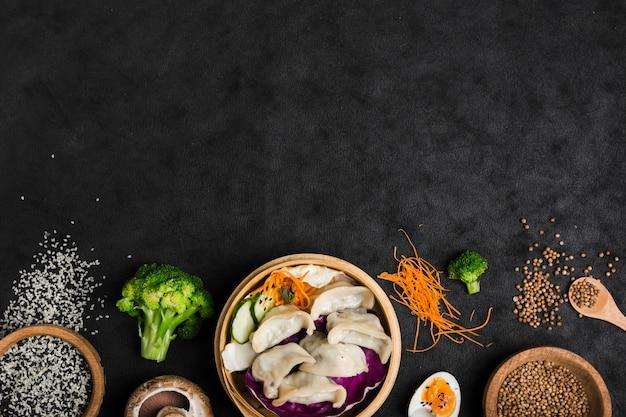 Gekookte dumplings in de bamboestoomboot met eieren; broccoli; sesam en korianderzaden op zwarte textuurachtergrond