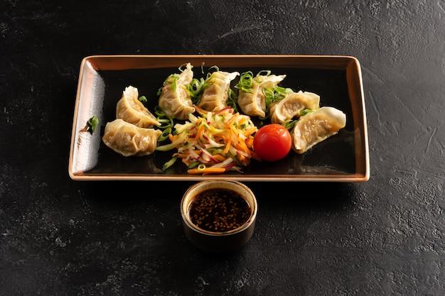 Gekookte dumplings met verse groenten, kool, radijs, wortelen, komkommer, groene uien en sojasaus met sesamzaadjes.