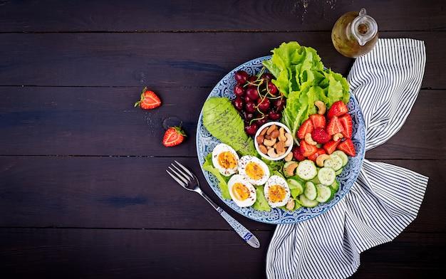 Gekookte eieren, avocado, komkommer, noten, kersen en aardbeien