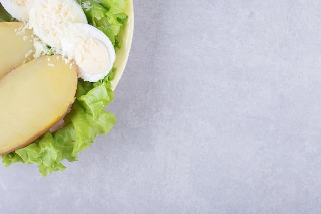 Gekookte eieren en aardappelen op gele plaat.