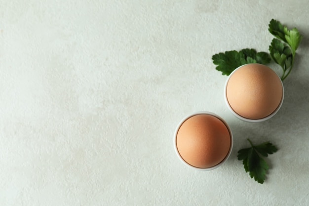 Gekookte eieren en peterselie op witte geweven lijst