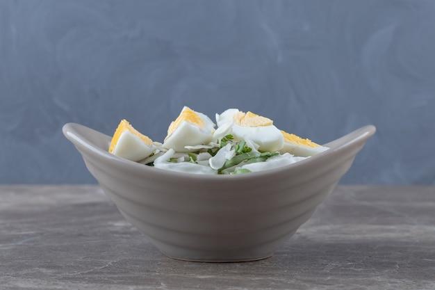 Gekookte eieren en verse salade in keramische kom.