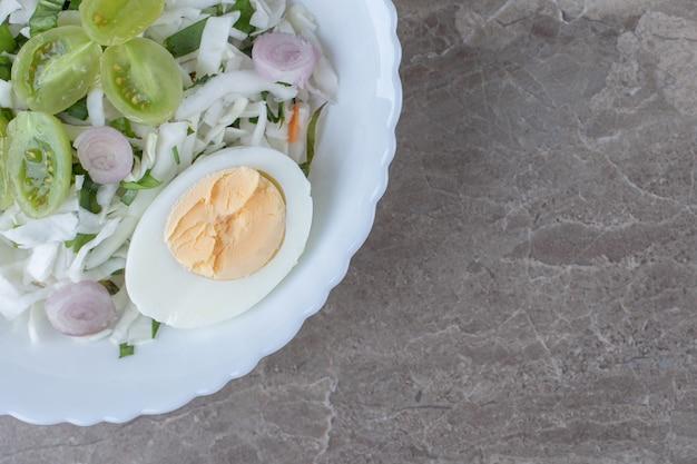 Gekookte eieren en verse salade op witte plaat.