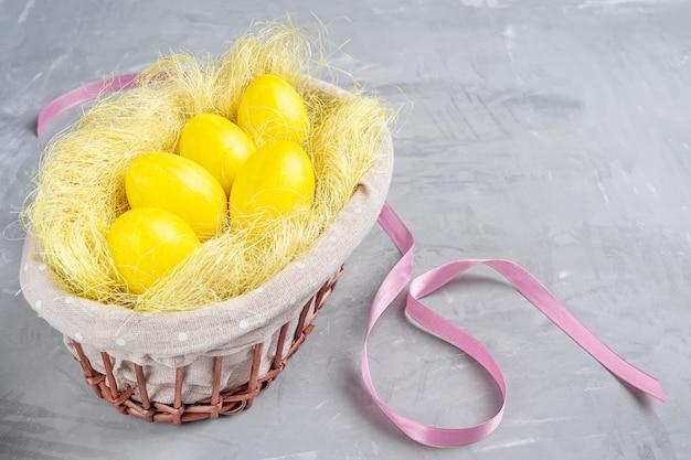 Gekookte eieren geschilderd in gele kleur in spalkmand met roze band op grijze betonnen tafel met pasen