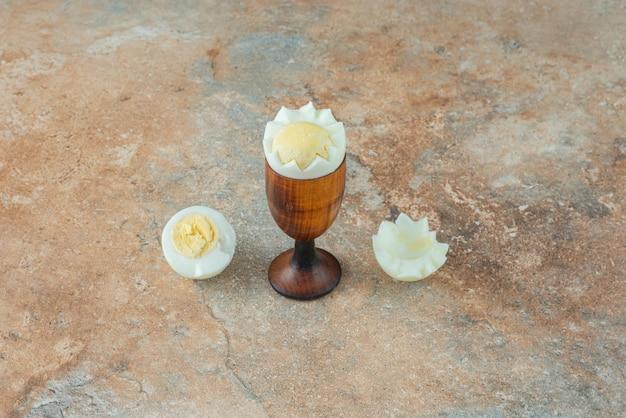 Gekookte eieren in eierdopje op marmeren tafel.