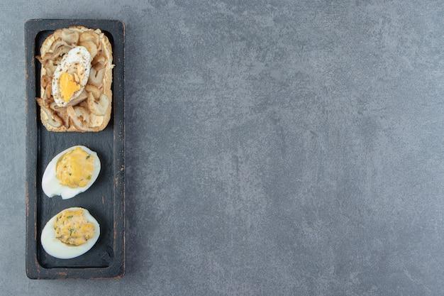 Gekookte eieren met brood op zwarte plaat.