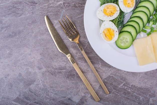 Gekookte eieren met een groene salade in een witte plaat.