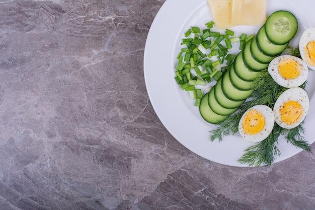 Gekookte eieren met gehakte kruiden en komkommers in een witte plaat