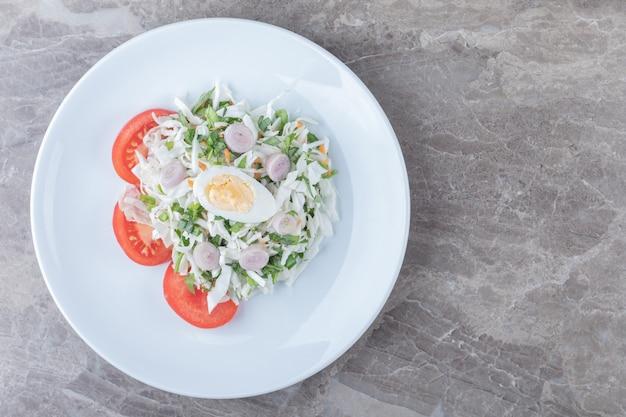 Gekookte eieren met groentesalade op witte plaat.
