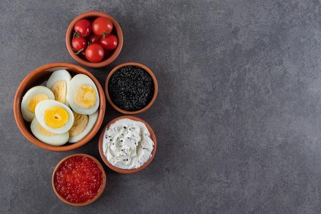 Gekookte eieren met rode en zwarte kaviaar die op een steenachtergrond wordt geplaatst.