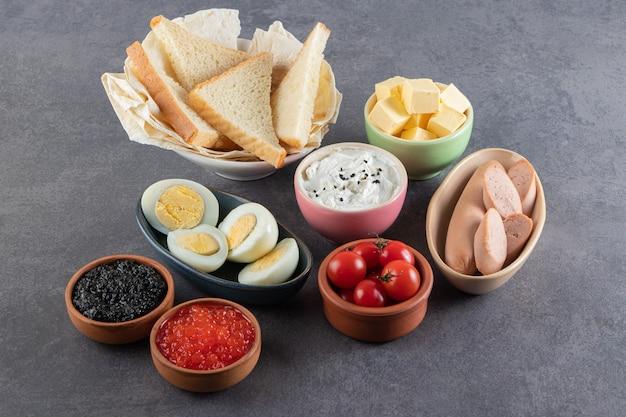 Gekookte eieren met rode en zwarte kaviaar op een stenen tafel.