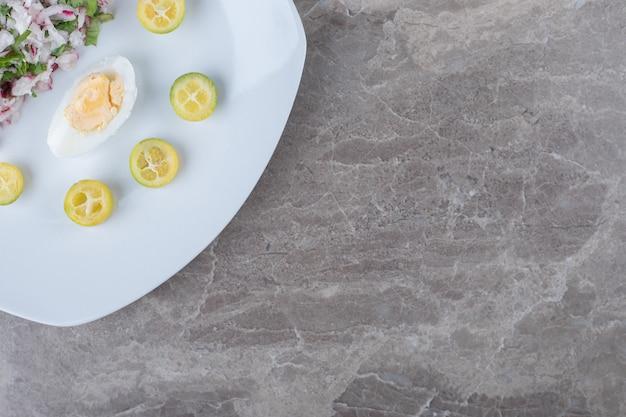 Gekookte eieren met salade als garnering op witte plaat.