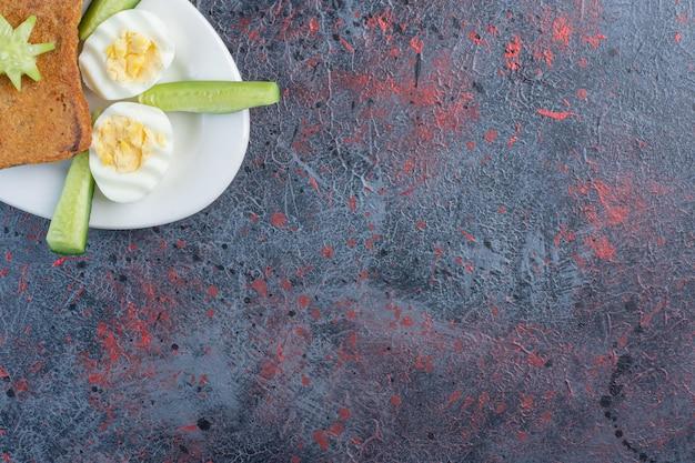 Gekookte eieren met sneetjes brood en komkommers.