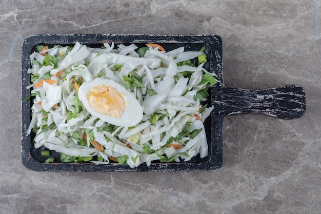 Gekookte eieren met verschillende verse in blokjes gesneden groenten op zwart bord.