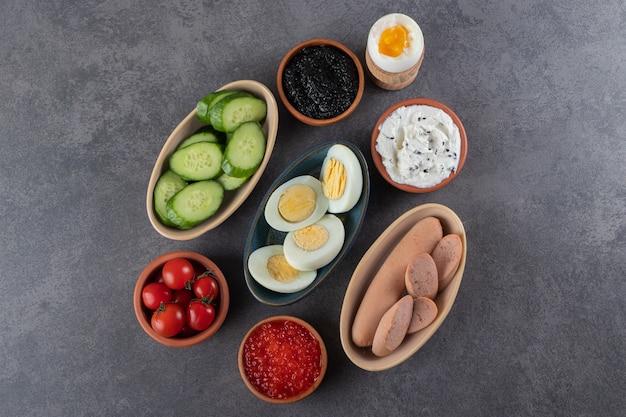 Gekookte eieren met verse komkommer en rode kerstomaatjes op stenen tafel.