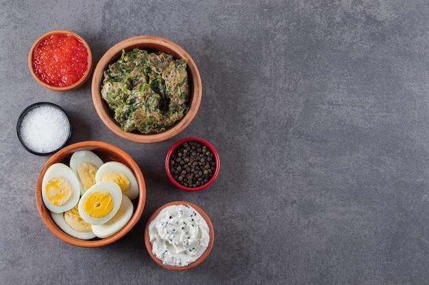 Gekookte eieren met zout en kaviaar op een stenen achtergrond.