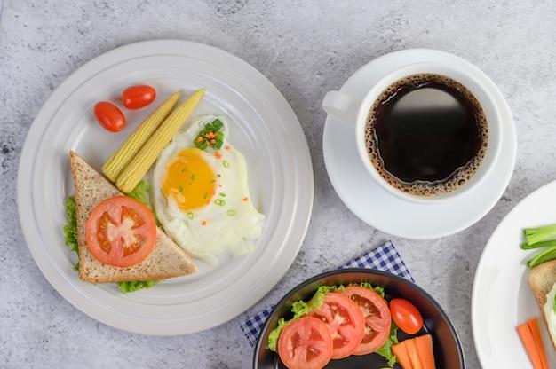 Gekookte eieren, wortelen en tomaten op een pan met tomaat op een houten lepel en koffiekopje.