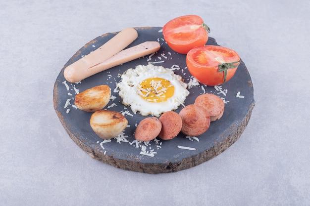 Gekookte en gebakken worstjes met ei op stuk hout.